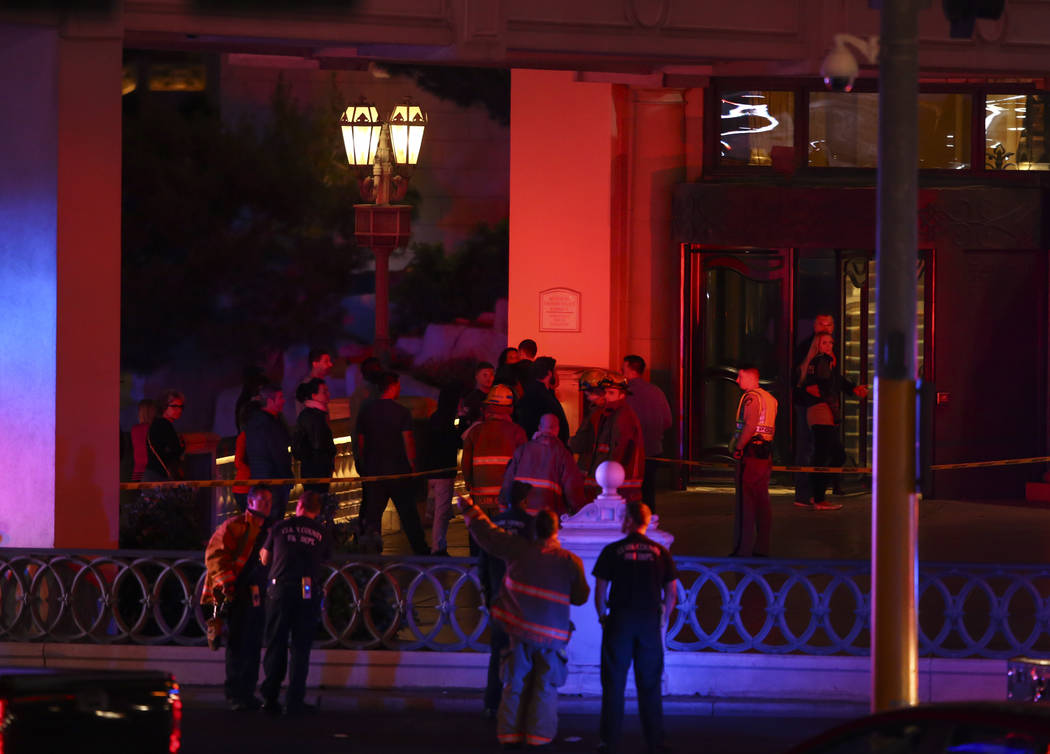 Pedestrians outside of the Bellagio hotel-casino as Clark County Fire Department and other emergency personnel respond after part of the roof of the hotel-casino caught fire in Las Vegas on Friday ...