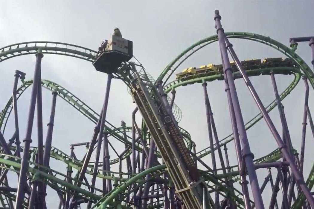 In this image made from a video provided by the Prince George's County Fire Department, firefighters respond to the scene after over a dozen people became stuck when a roller coaster stalle ...