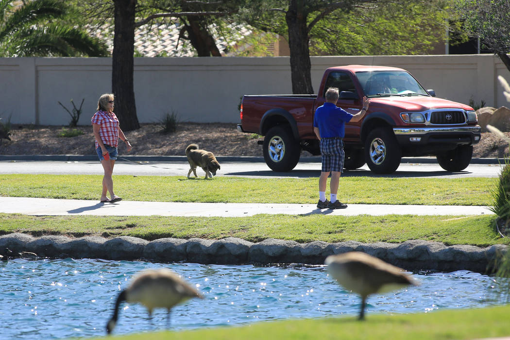 A couple walk their dog along a lake at Desert Shores on Friday, April 14, 2017. (Brett Le Blanc Las Vegas Review-Journal) @bleblancphoto