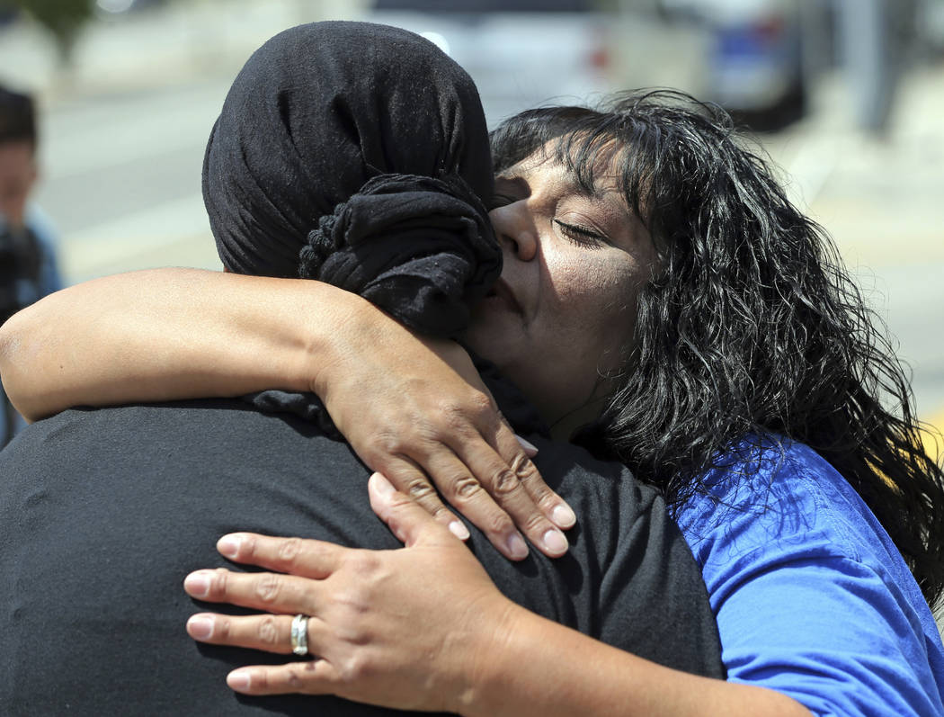 After leading a prayer group, Marie Cabrera, right, embraces one of the group members near a sidewalk memorial dedicated to the teacher and student who were shot to death Monday at North Park Elem ...