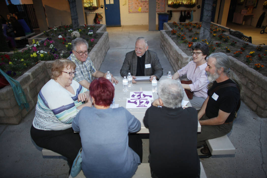 A group led by Father Jamie Conrad, center, discusses personal immigration or migration stories after an immigration forum hosted by the Nevadans for the Common Good on Monday, April 17, 2017, at  ...