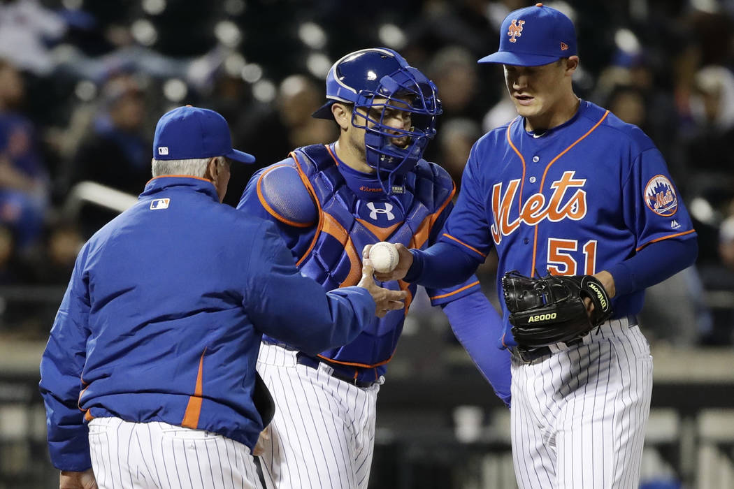New York Mets manager Terry Collins, left takes pitcher Paul Sewald, right, out of the game as catcher Travis d'Arnaud watches during the eighth inning of a baseball game against the Miami Marlins ...