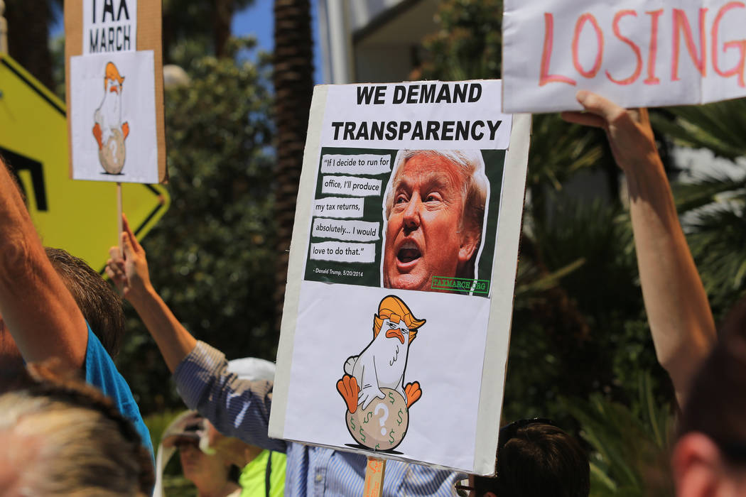 Demonstrators hold signs in an effort to get President Donald Trump to release his tax returns during a tax day protest at Trump International Hotel on Saturday, April 15, 2017. Brett Le Blanc Las ...