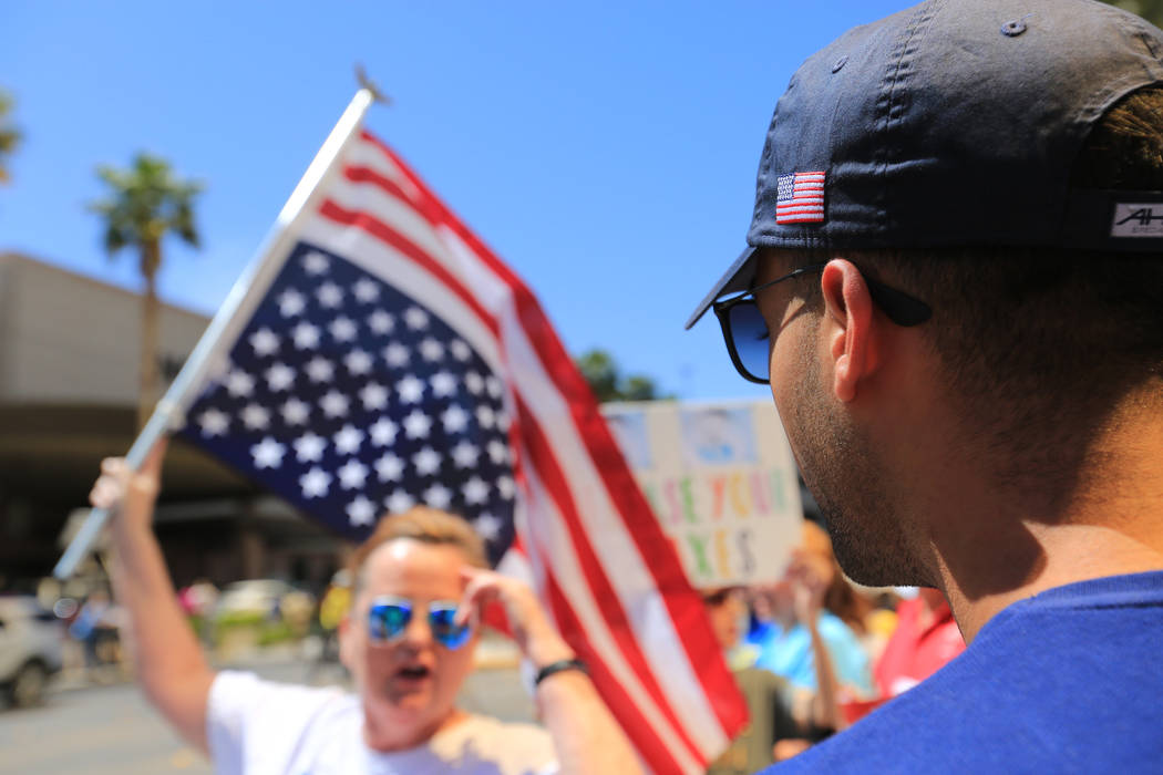 """Daniel Naccarati, right, wearing hat with """"Trump"""" and an American flag on it talks with Coleen Brola, who is carrying an upside down American flag, during a tax day protest at Tr ..."""