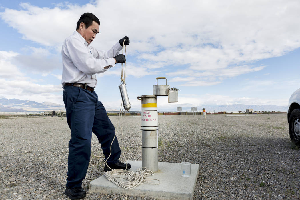 Water Quality Monitoring Field Specialist Daniel Luong utilizes a vessel to acquire a water sample from the 20 million water reservoir located at Montessori Street and Warm Springs Road, Las Vegas ...