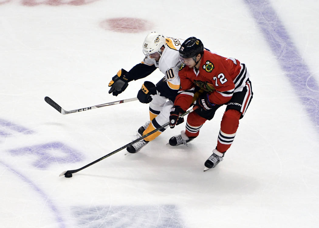 Nashville Predators center Colton Sissons (10) and Chicago Blackhawks left wing Artemi Panarin (72) go for the puck during the first period in Game 2 of a first-round NHL hockey playoff series, Sa ...
