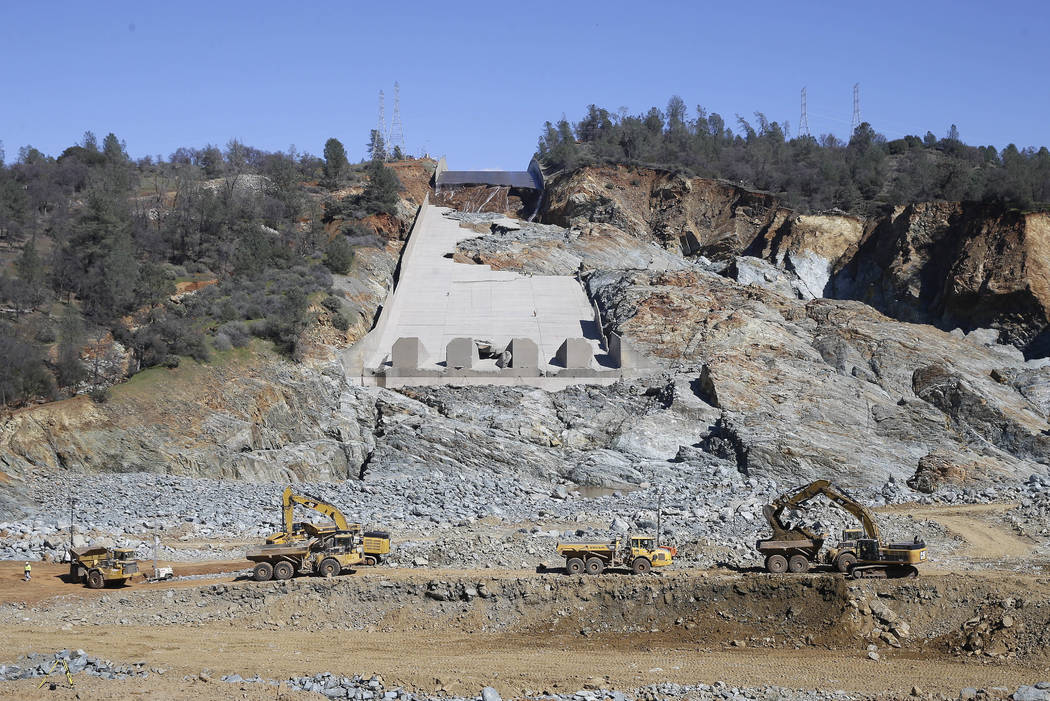 """In this Feb. 28, 2017, file photo, construction crews clear rocks away from Oroville Dam's crippled spillway in Oroville, Calif. A team of experts is warning of a """"very significant risk"""" if the ma ..."""