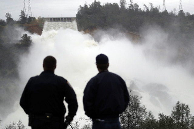 Two men watch as water gushes from the Oroville Dam's main spillway Wednesday, Feb. 15, 2017, in Oroville, Calif. The Oroville Reservoir is continuing to drain Wednesday as state water officials s ...