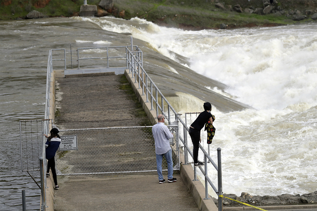 People watch the gushing waters of the Feather River from the town's fish hatchery a day after an evacuation was lifted Wednesday, Feb. 15, 2017, in Oroville, California. Authorities say the immed ...