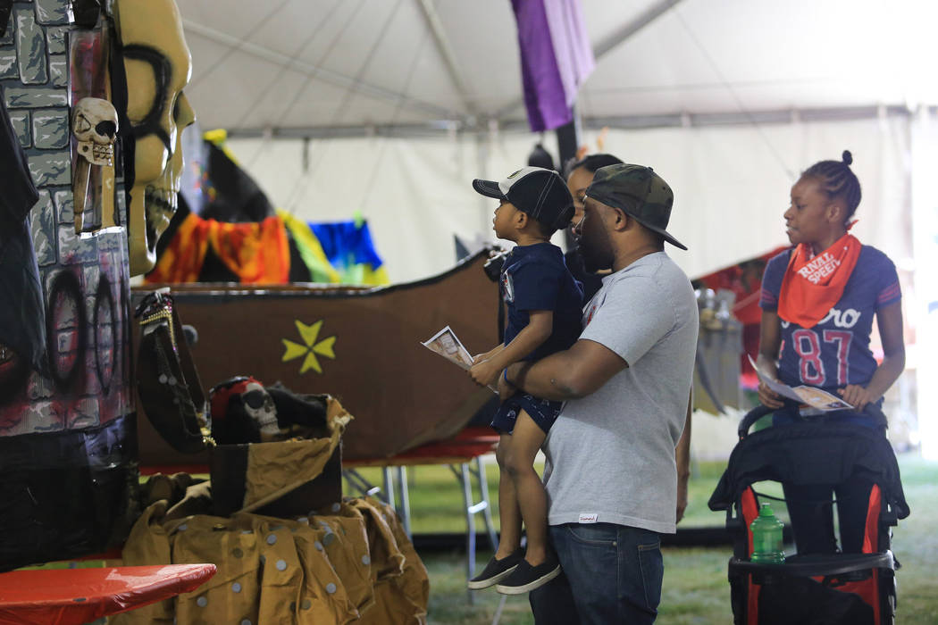 Brandon Austin lifts his son Elijah Austin for a better view of ships in the cardboard regatta during Pirate Fest 2017 at Craig Ranch Regional Park on Friday, April 21, 2017. Brett Le Blanc Las Ve ...