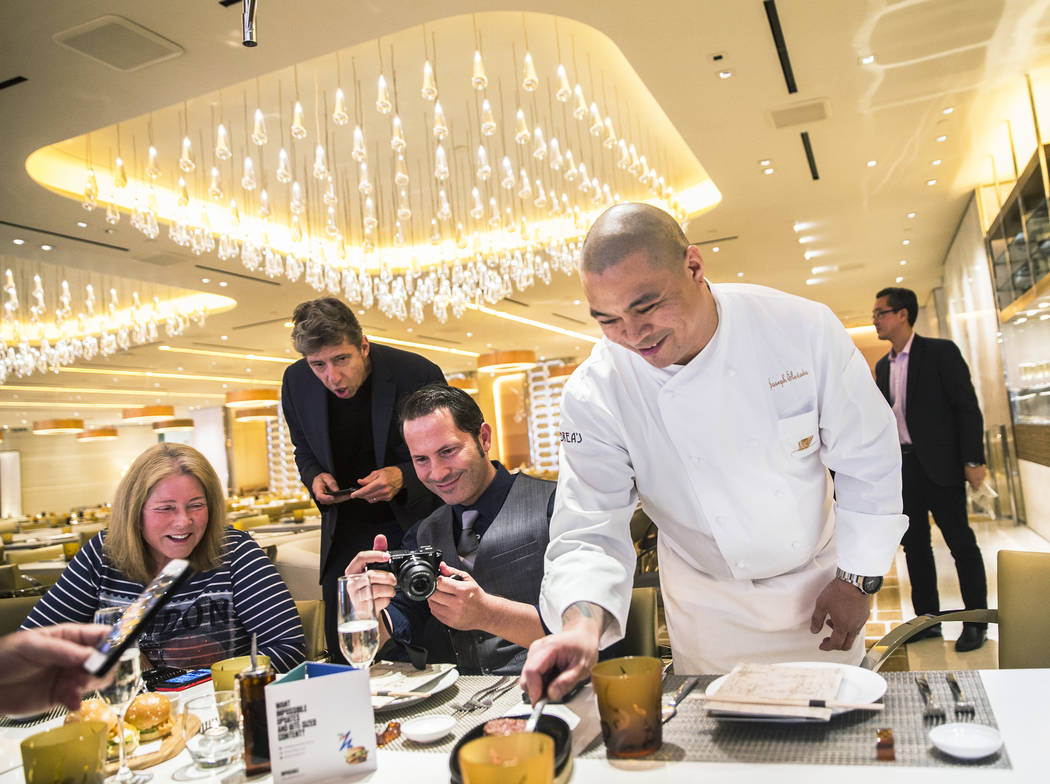 Chef Joseph Elevado, right, serves impossible burgers, made with frisee, kimchee, pickles, kalbi sauce and kochujang aioli at Andrea's at Encore at the Wynn Las Vegas hotel-casino, on Friday, Apri ...