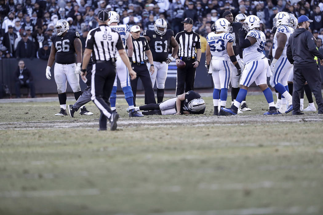 Oakland Raiders quarterback Derek Carr, bottom, remains on the field after being tackled by Indianapolis Colts inside linebacker Edwin Jackson during the second half of an NFL football game in Oak ...