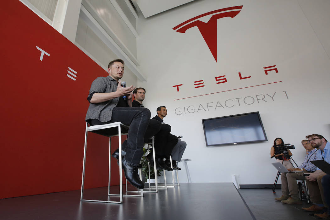 Elon Musk, CEO of Tesla Motors Inc., left, discusses the company's new Gigafactory Tuesday, July 26, 2016, in Sparks, Nev. (AP Photo/Rich Pedroncelli)