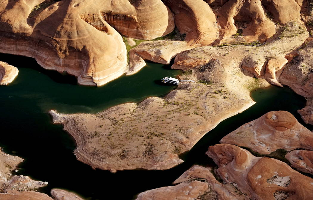 A houseboat camps on the shore in shallow water in a canyon at Lake Powell near Page, Ariz., May 26, 2015. Lake Powell on the Colorado River provides water for Nevada, Arizona and California. A se ...