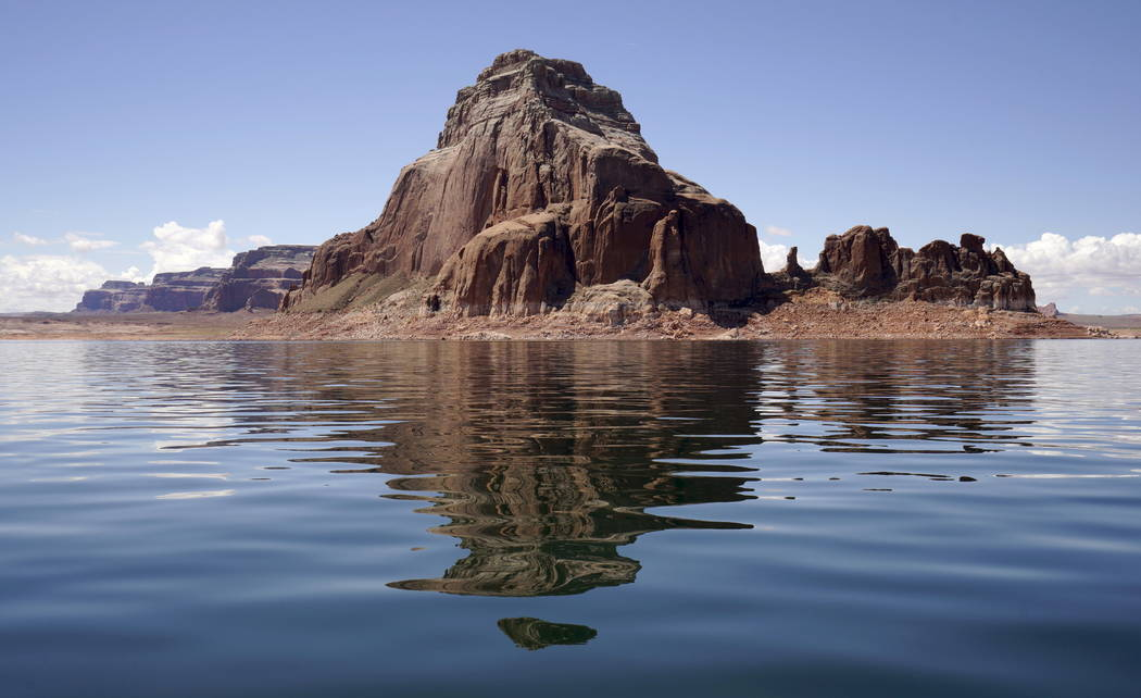 Gregory Butte is reflected in Lake Powell near Page, Ariz., May 25, 2015. Lake Powell on the Colorado River provides water for Nevada, Arizona and California. A severe drought in recent years, com ...
