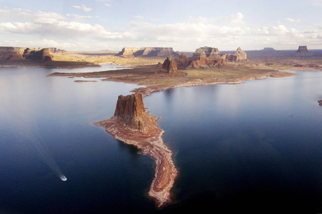 A boat makes its way around Padre Butte in Lake Powell near Page, Ariz., May 26, 2015. Lake Powell on the Colorado River provides water for Nevada, Arizona and California. A severe drought in rece ...