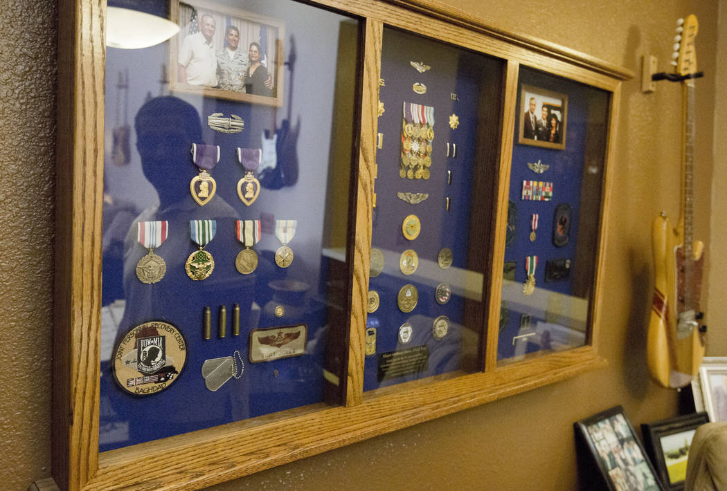 Author and former Air Force major Anthony Jones suffers from major brain injuries from Iraq, looks at his shadow box of medals and memorabilia from his time in service in his home in Las Vegas, We ...