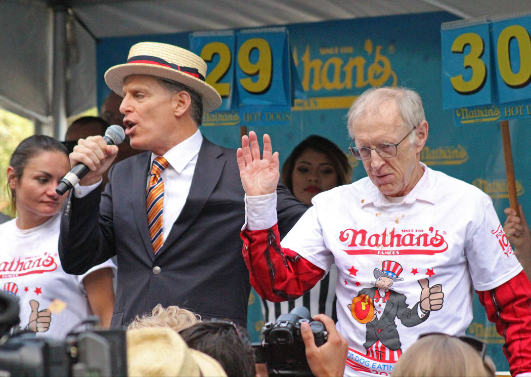 Event emcee George Shea, left, announces Rich LeFevre, 73, right, as the winner of the Nevada qualifier for the Fourth of July International Hot Dog-Eating Contest at New York New York hotel-casin ...
