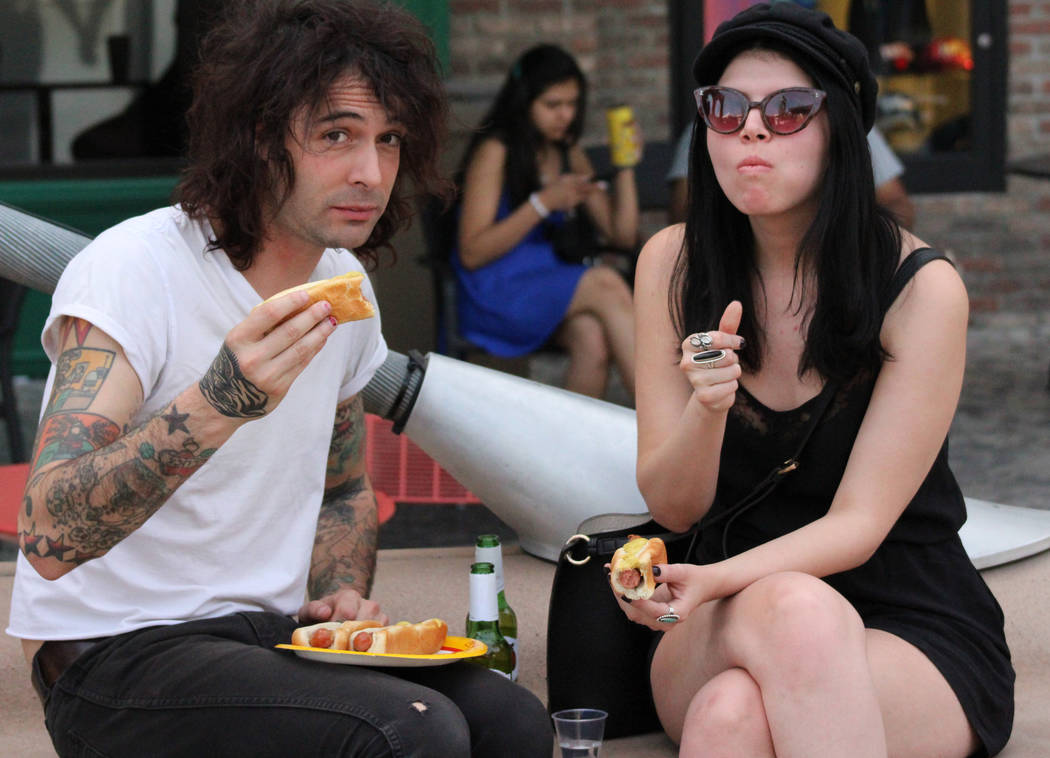 Zach, left, and Nicole, who chose not to give their last names, chow down on the leftover hot-dogs from the Nevada qualifier for the Fourth of July International Hot Dog-Eating Contest at New York ...