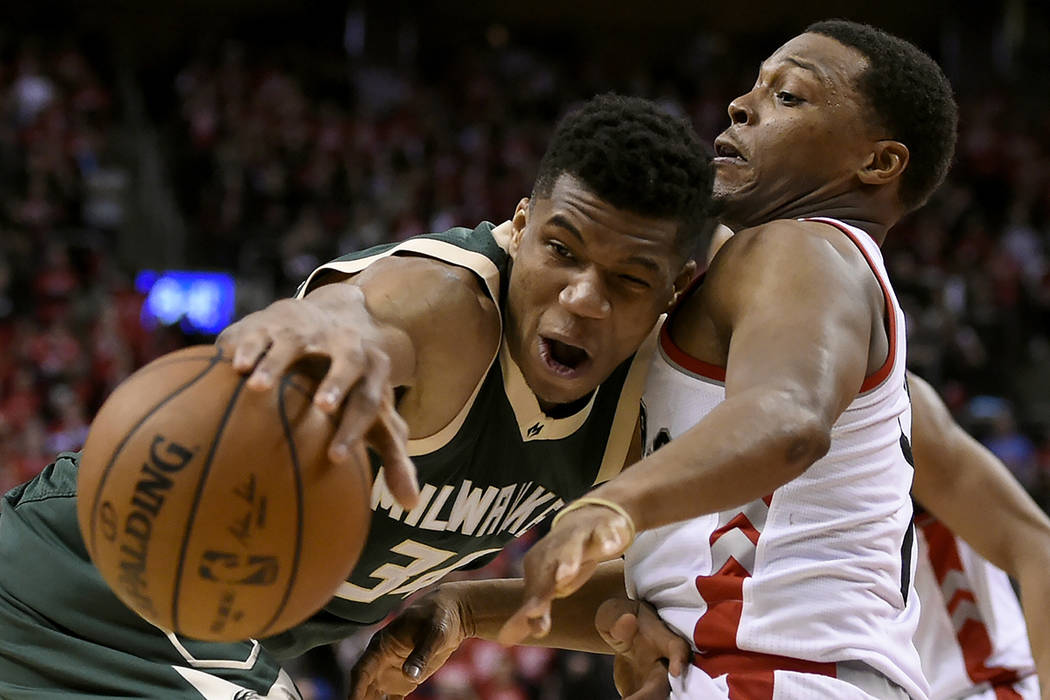 Toronto Raptors guard Kyle Lowry (7) defends as Milwaukee Bucks forward Giannis Antetokounmpo (34) tries to move the ball during the second half of Game 2 of an NBA basketball first-round playoff  ...