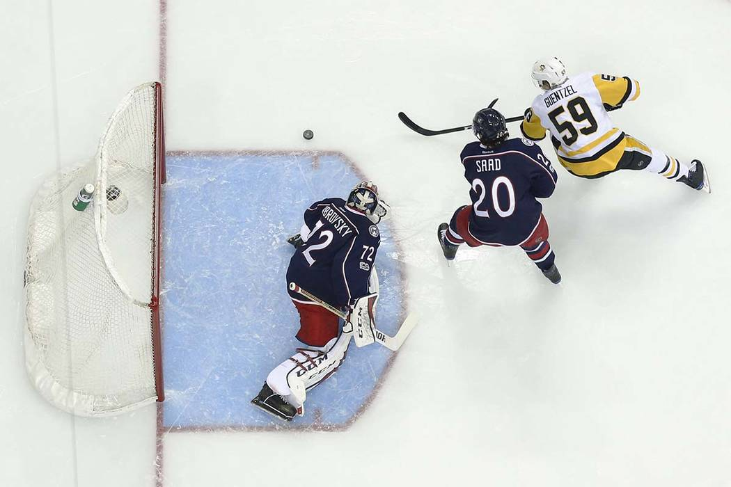Columbus Blue Jackets' Sergei Bobrovsky, left, of Russia, makes a save as teammate Brandon Saad defends against Pittsburgh Penguins' Jake Guentzel during the first period of Game 4 of an NHL first ...