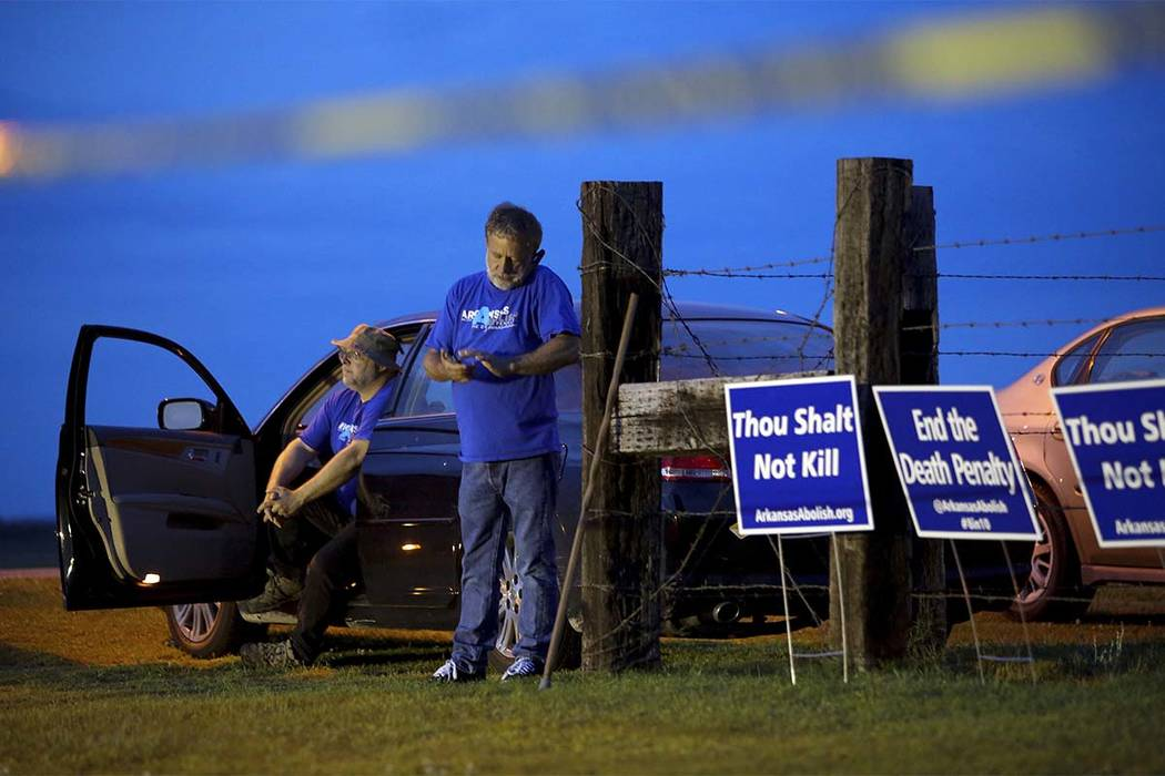 """Anti-death penalty supporters Abraham Bonowitz, left, and Randy Gardner wait near their taped off """"protest corral"""" outside the Varner Unit late Monday, April 17, 2017 near Varner ..."""