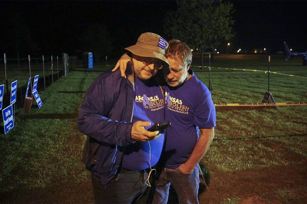 """Anti-death penalty supporter Randy Gardner, right, embraces Abraham Bonowitz after they read on his phone the 11:45 p.m., decision to halt the execution in their taped off """"protest corral"""" outside ..."""
