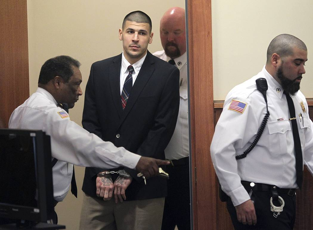 In this Monday, Dec. 23, 2013, file photo, former New England Patriots NFL football player Aaron Hernandez is led into his court appearance at the Fall River Superior Court in Fall River, Mass. Ma ...
