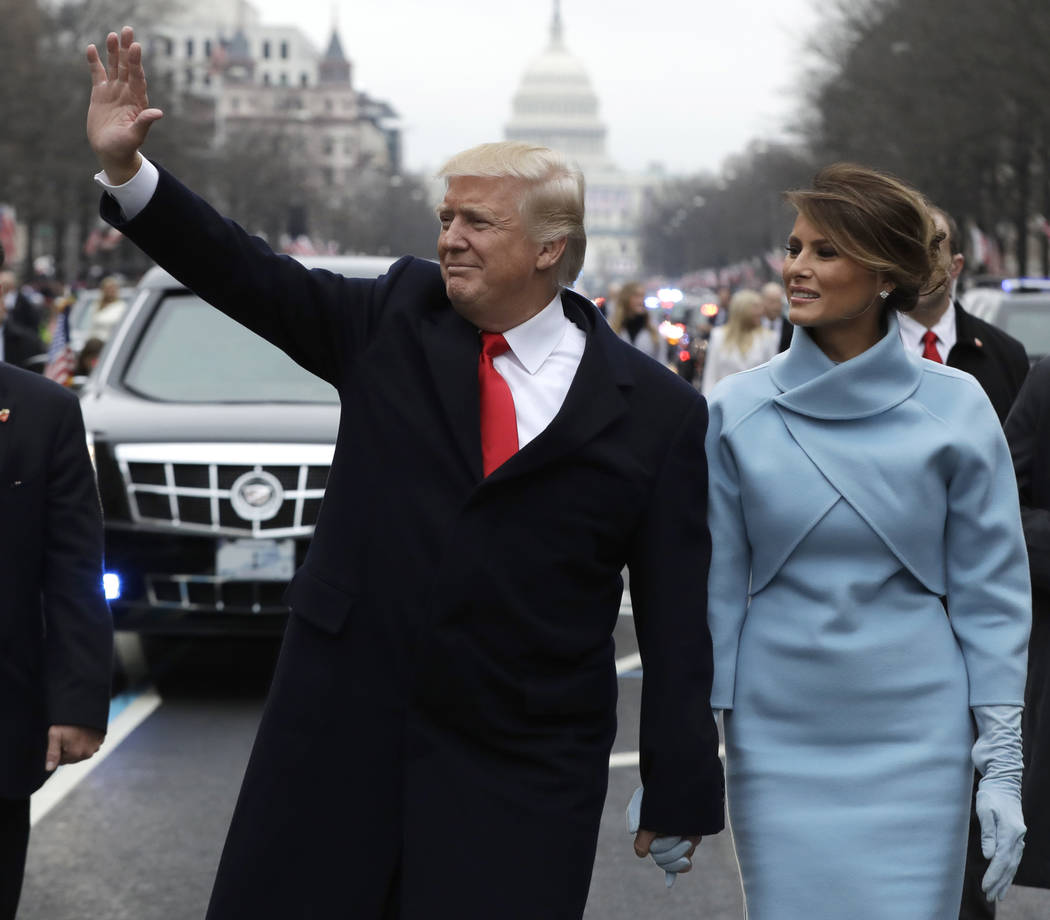 President Donald Trump waves as he walks with first lady Melania Trump during the inauguration parade on Pennsylvania Avenue in Washington on Jan. 20, 2017. Evan Vucci/AP, Pool