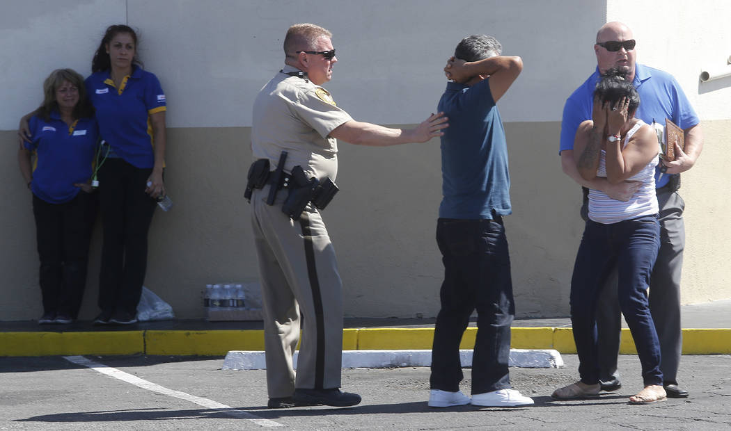People react after arriving to a crime scene where a stabbing occurred at the Arco gas station located on Bonanza Rd. and N Lamb Blvd. on Wednesday, April 19, 2017, in Henderson. One person has di ...