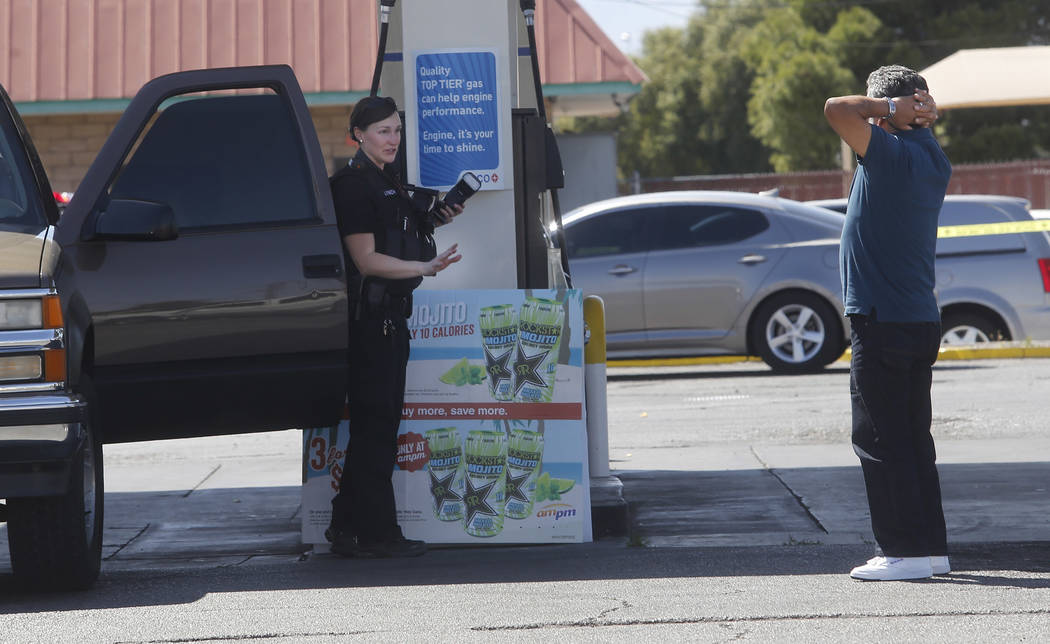 A crime scene investigator attempts to calm a man as he reacts after arriving to a crime scene where a stabbing occurred at the Arco gas station located on Bonanza Rd. and N Lamb Blvd. on Wednesda ...