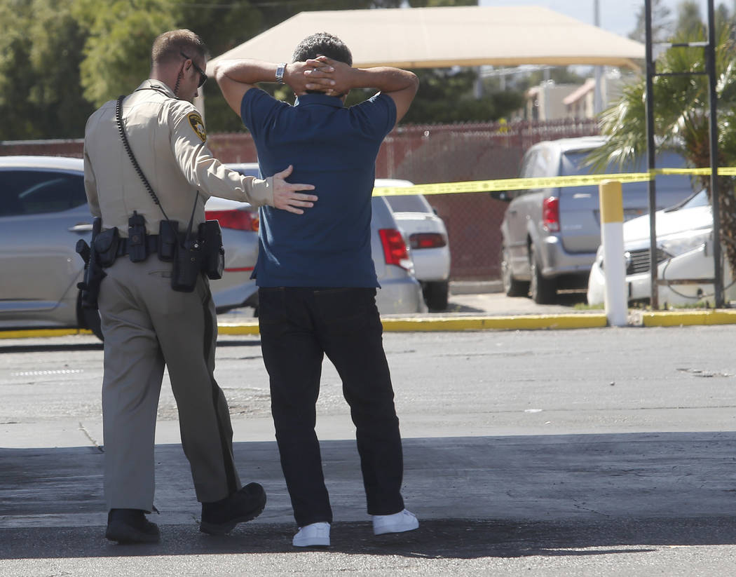 A Las Vegas Metropolitan Department police officer attempts to calm a man as he reacts after arriving to a crime scene where a stabbing occurred at the Arco gas station located on Bonanza Rd. and  ...
