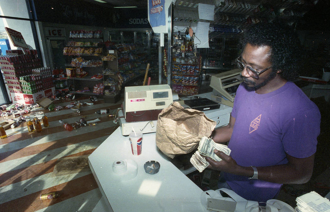 Henry Clark, owner of Rick-E Quick Food Mart in North Las Vegas, holds a bag of money that was returned to him by looters on May 1, 1992, the morning after the west Las Vegas riots.