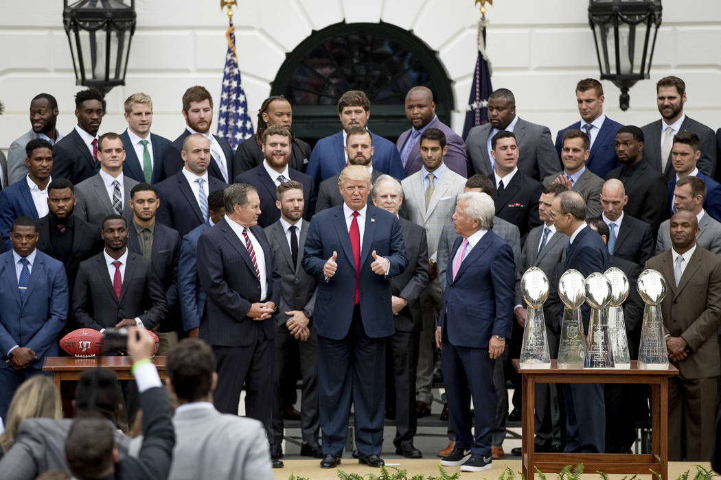 President Donald Trump stands with New England Patriots head coach Bill Belichick, left, New England Patriots owner Robert Kraft, right, and members of the New England Patriots during a ceremony o ...