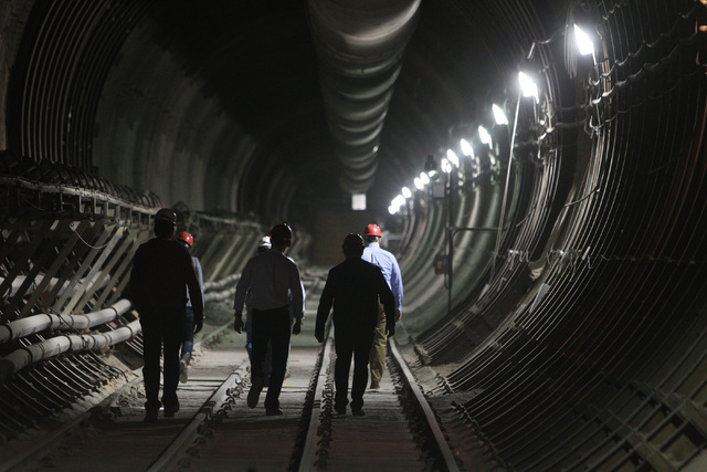 Congressional staff members, media and Department of Energy employees head for the south portal entrance during a congressional tour of the Yucca Mountain exploratory tunnel Thursday, April 9, 201 ...