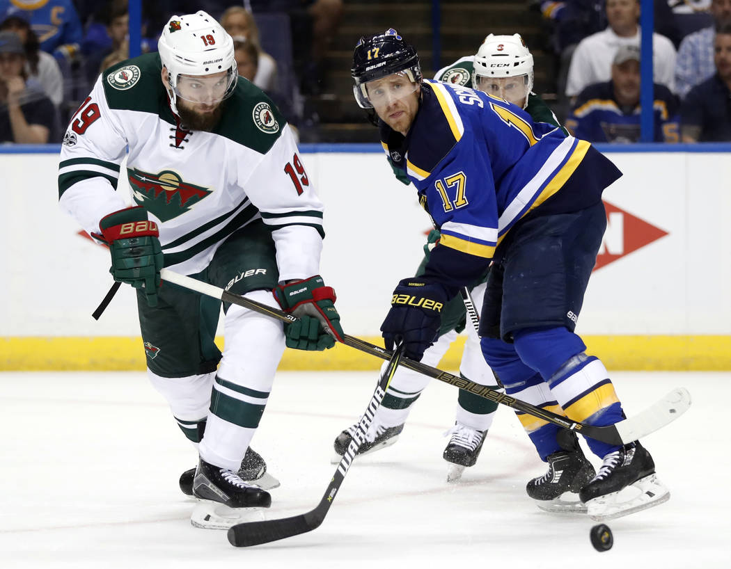 Minnesota Wild's Martin Hanzal, of the Czech Republic, and St. Louis Blues' Jaden Schwartz, right, chase the loose puck during the second period in Game 4 of an NHL hockey first-round playoff seri ...