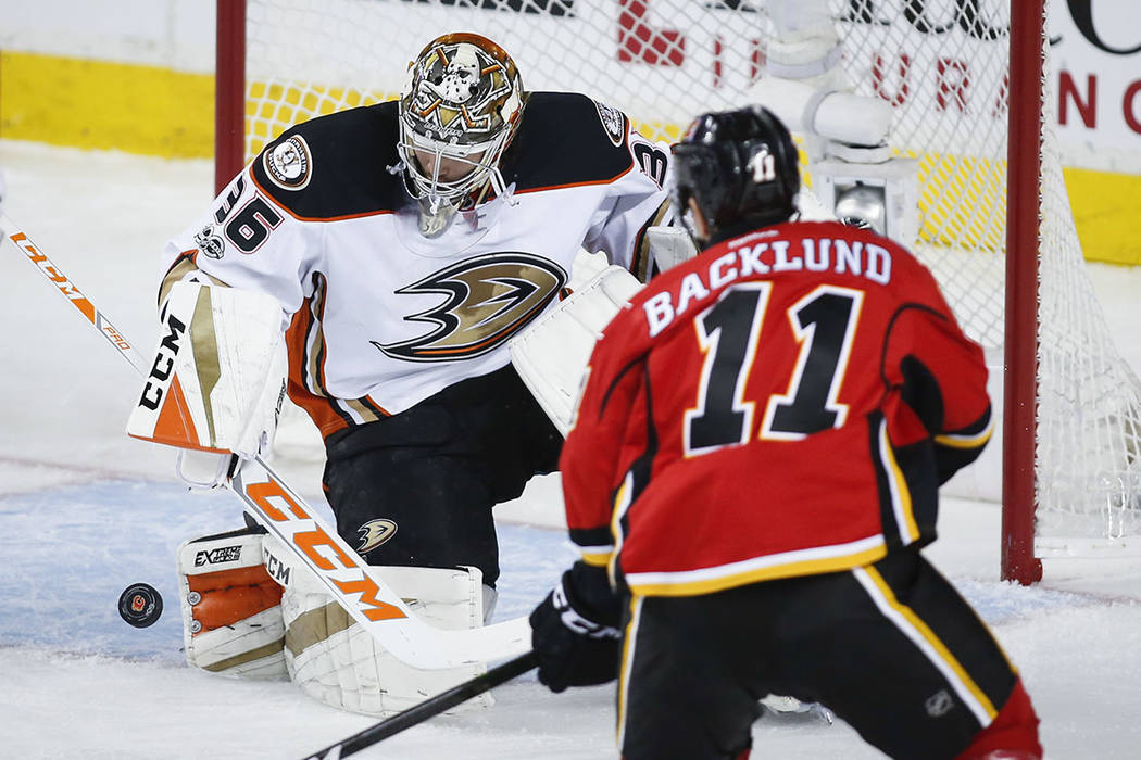 Anaheim Ducks goalie John Gibson, left, deflects a shot from Calgary Flames' Mikael Backlund, of Sweden, during the second period of Game 4 in a first-round NHL hockey Stanley Cup playoff series W ...