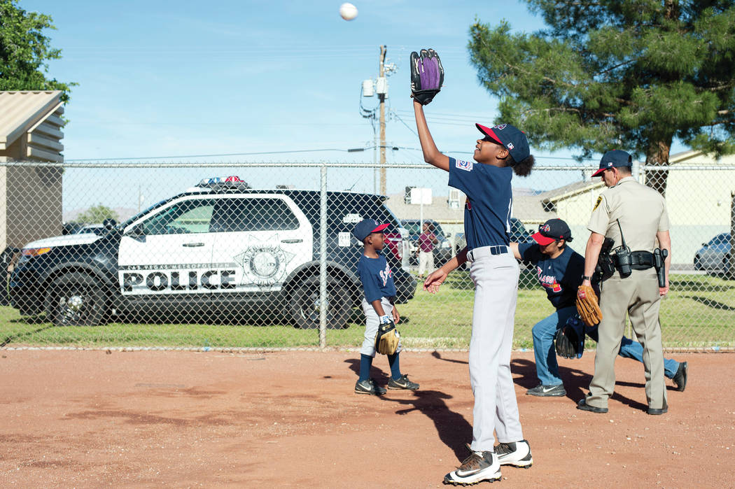 Bridget Bennett Las Vegas Review-Journal @bridgetkbennett Alayja Grayson, 11, warms up with teammates as Metro officer Dave Shive coaches them before a Bolden Little League game Thursday at  ...