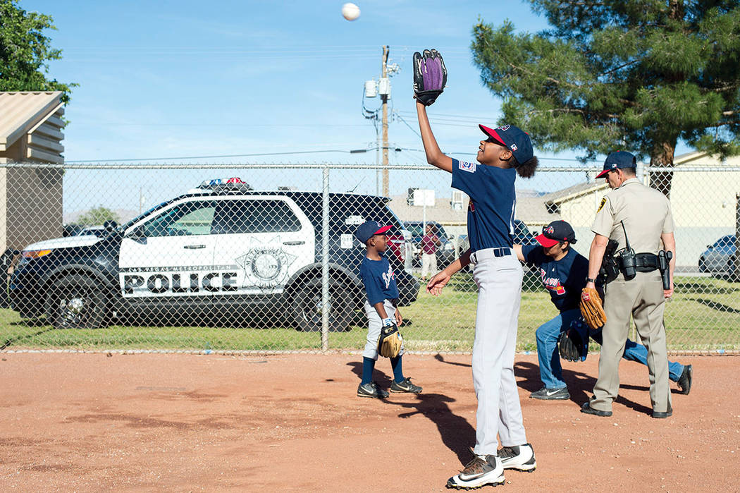 Alayja Grayson, 11, warms up with teammates as Metro officer Dave Shive coaches them before a Bolden Little League game Thursday at Doolittle Field. Bolden Little League, co-founded by Mario Berla ...
