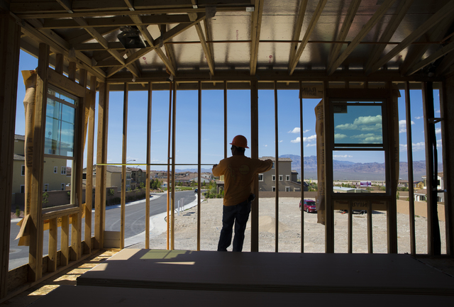 Benjamin Hager/RJNewHomes.Vegas Jose Juarez measures a wall panel in a three-story home being constructed in the Skye Canyon May 23.