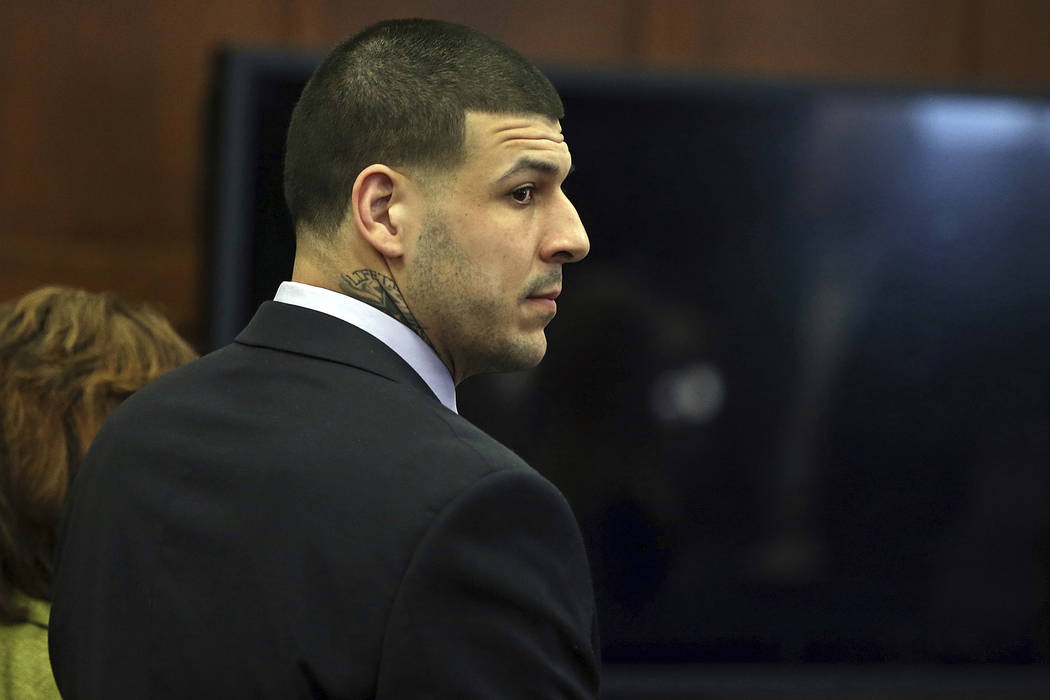 Former New England Patriots tight end Aaron Hernandez stands at the defense table when court is adjourned without a verdict on day five of jury deliberations in his double murder trial at Suffolk  ...