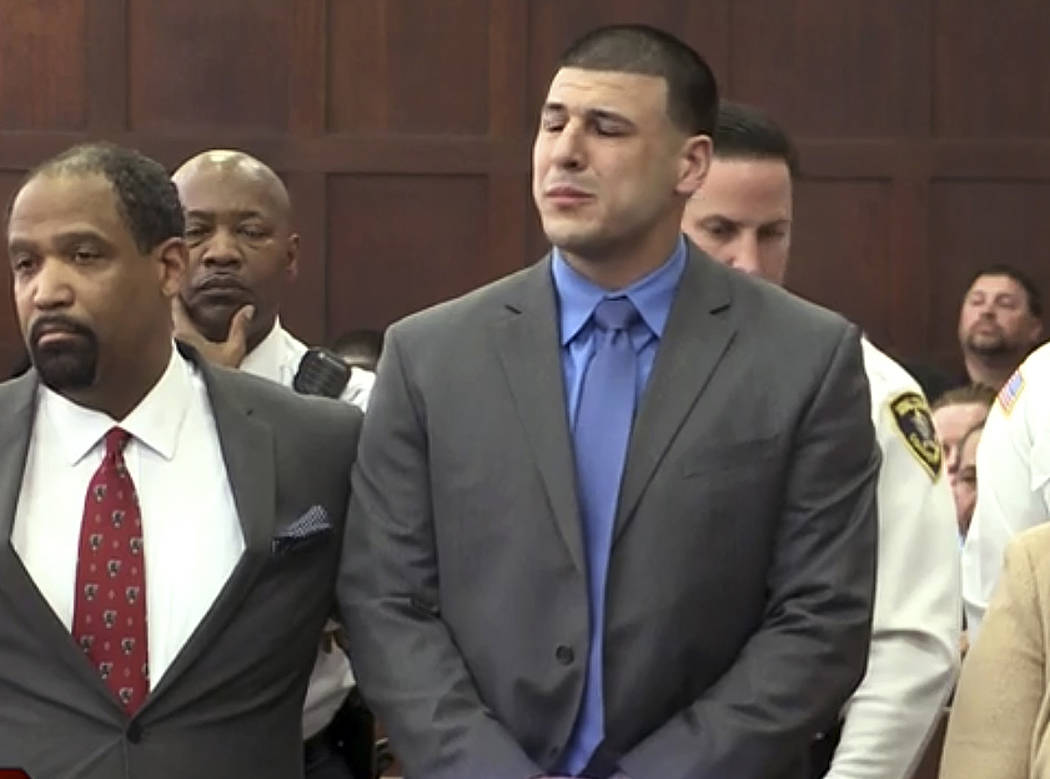 In this still image from video, Aaron Hernandez, right, listens beside defense attorney Ronald Sullivan, Friday, April 14, 2017, in court in Boston, as he is pronounced not guilty of murder in the ...