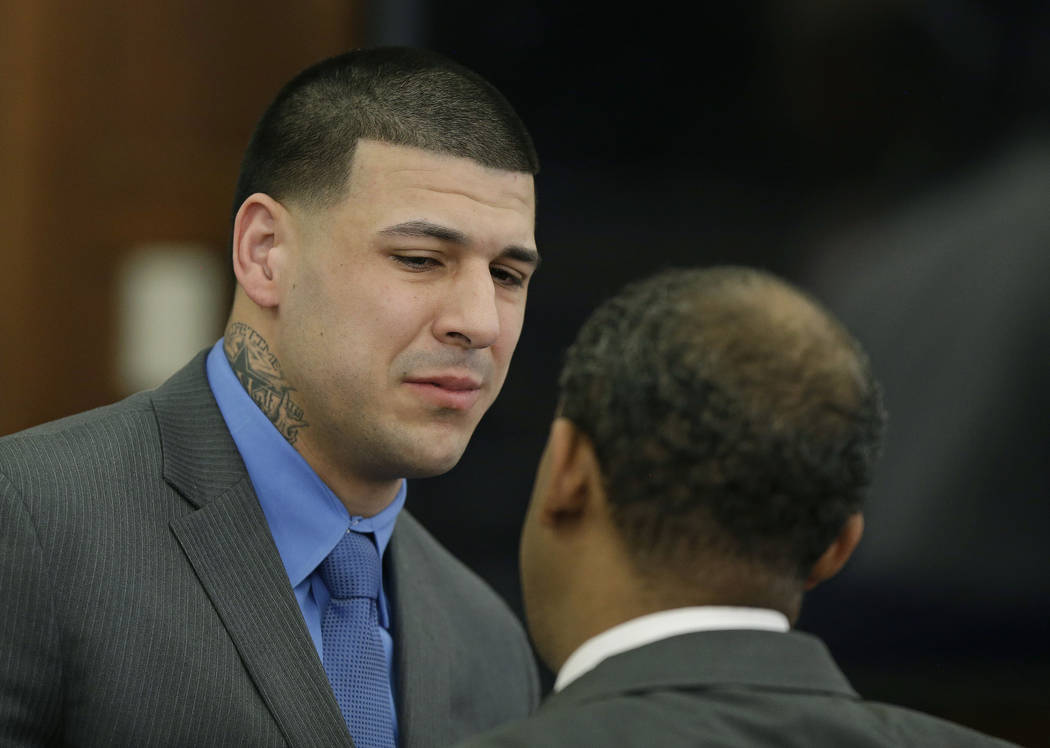 Former New England Patriots tight end Aaron Hernandez cries as he turns to defense attorney Ronald Sullivan reacting to his double murder acquittal at Suffolk Superior Court Friday, April 14, 2017 ...