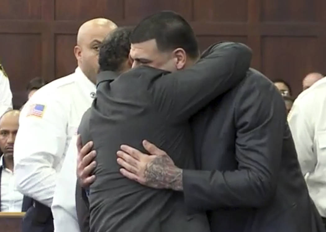 In this still image from video, Aaron Hernandez, center, is hugged by defense attorney Ronald Sullivan, Friday, April 14, 2017, in court in Boston, after being found not guilty of murder in the 20 ...