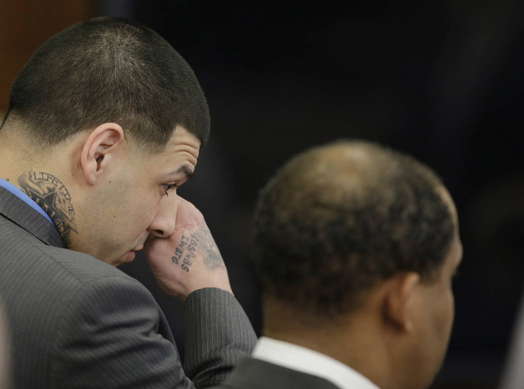 Former New England Patriots tight end Aaron Hernandez wipes tears from his eyes as he stands with defense attorney Ronald Sullivan reacting to his double murder acquittal at Suffolk Superior Court ...