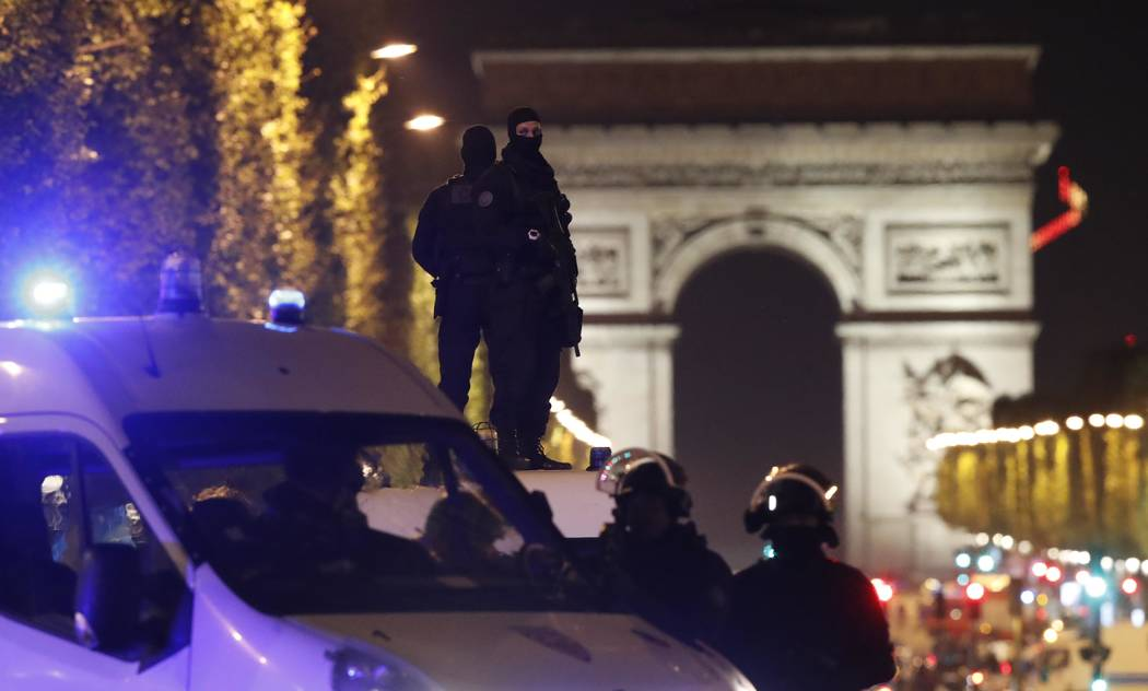 Masked police stand on top of their vehicle on the Champs Elysees Avenue after two policemen were killed and another wounded in a shooting incident in Paris, France, April 20, 2017. (Christian Har ...