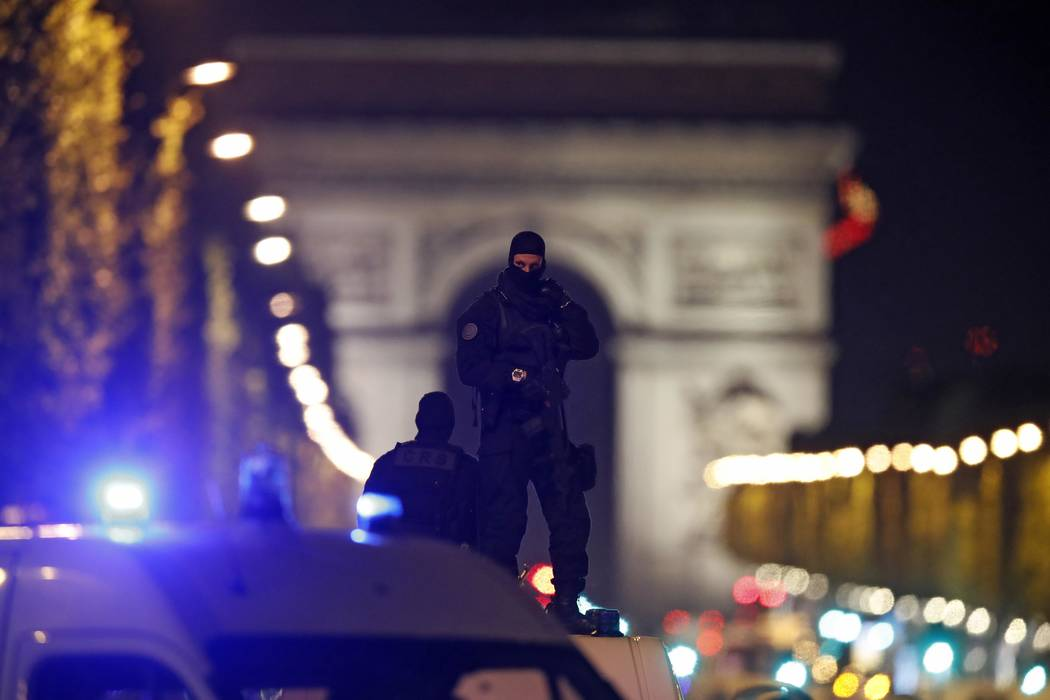 Masked police stand on top of their vehicle on the Champs Elysees Avenue after two policemen were killed and another wounded in a shooting incident in Paris, France, April 20, 2017. REUTERS/Christ ...