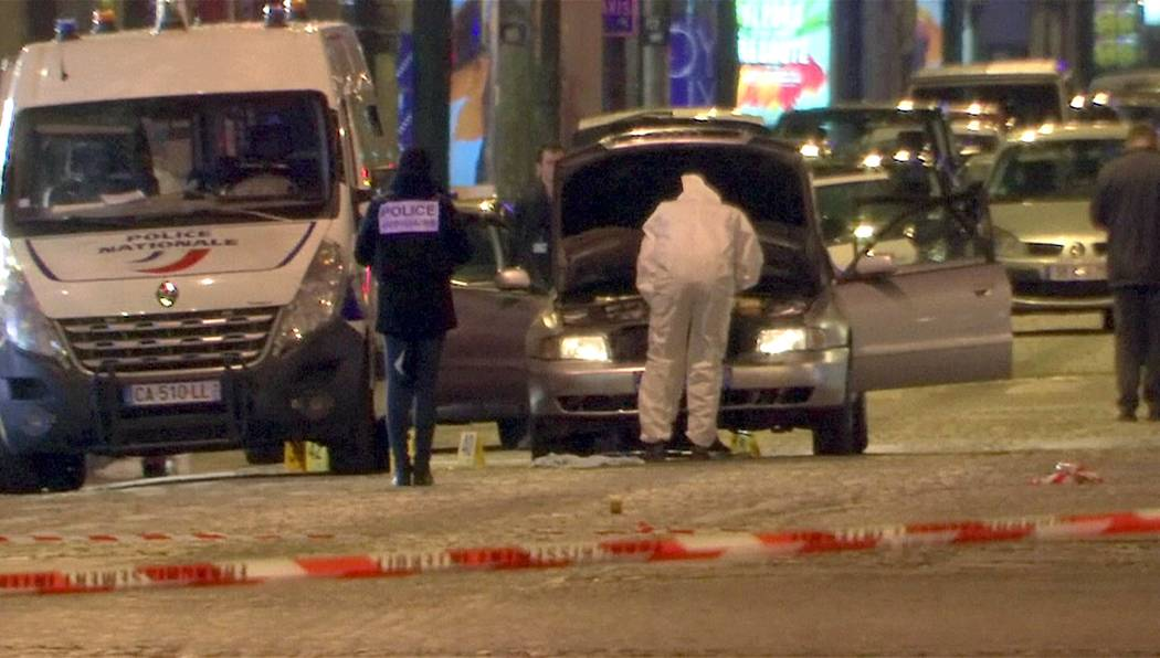 A still image from video footage shows Police investigators inspect the car used by the attacker  on the Champs Elysees Avenue after two policemen were killed and another wounded in a shooting inc ...