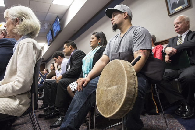Aleczandar Guzman, a member of the Paiute Tribe, holds a hand drum while listening to officials on the Senate Government Affairs Committee discuss a resolution to replace Columbus Day with Indigen ...