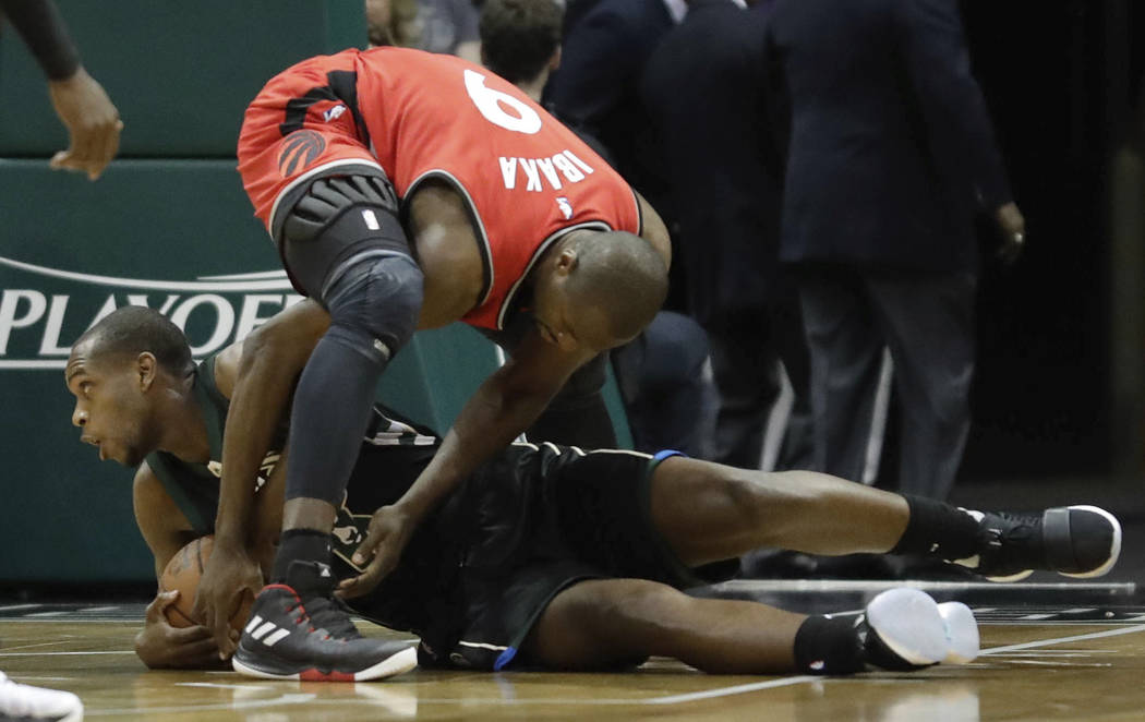 Toronto Raptors' Serge Ibaka and Milwaukee Bucks' Khris Middleton battle for a loose ball during the first half of game 3 of their NBA first-round playoff series basketball game Thursday, April 20 ...
